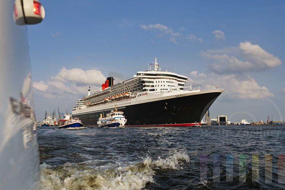 """Das Kreuzfahrtschiff """"Queen Mary 2"""" laeuft aus dem Hamburger Hafen aus, zahlreiche kleine Schiffe begleiten den Luxusliner. An Deck stehen winkende Passagiere, sonnig"""