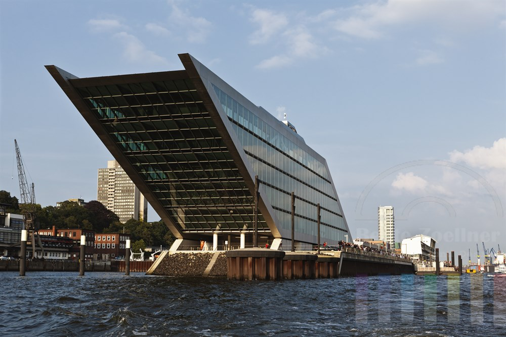 Das markante Gebaeude in Hamburg an der Elbe, wasserseits fotografiert, sonnig. Zahlreiche Menschen saeumen das Elbufer, weil gerade das Kreuzfahrtschiff Queen Mary 2 den Hamburger Hafen verlaesst.
