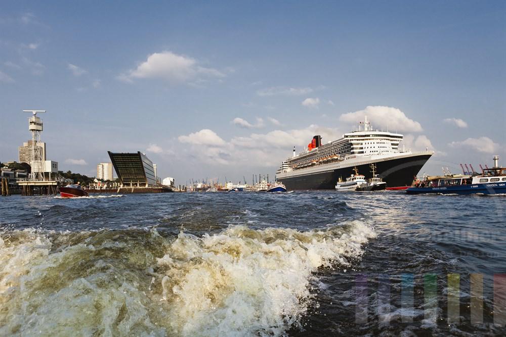 """Das Kreuzfahrtschiff """"Queen Mary 2"""" laeuft aus dem Hamburger Hafen aus, zahlreiche kleine Schiffe begleiten den Luxusliner, sonnig"""