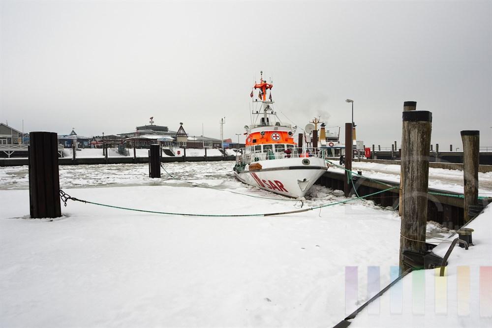 """Winter im Hafen von List/Sylt. Der Seenotrettungskreuzer """"Minden"""" liegt im vereisten Hafenbecken fest,"""