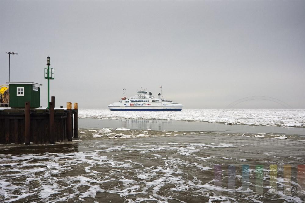 Sylt-Fähre fährt durch die Eisschollen auf der Nordsee und steuert den Hafen List/Sylt an, Himmel vedeckt