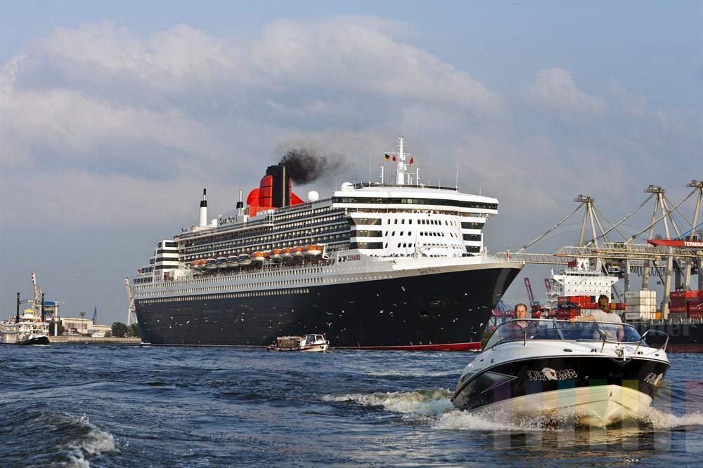"""Das Kreuzfahrtschiff """"Queen Mary 2"""" laeuft aus dem Hamburger Hafen aus, zahlreiche kleine Schiffe begleiten den Luxusliner. Zahlreiche Boote und ein grosser Moewenschwarm begleiten den Luxusliner, sonnig"""