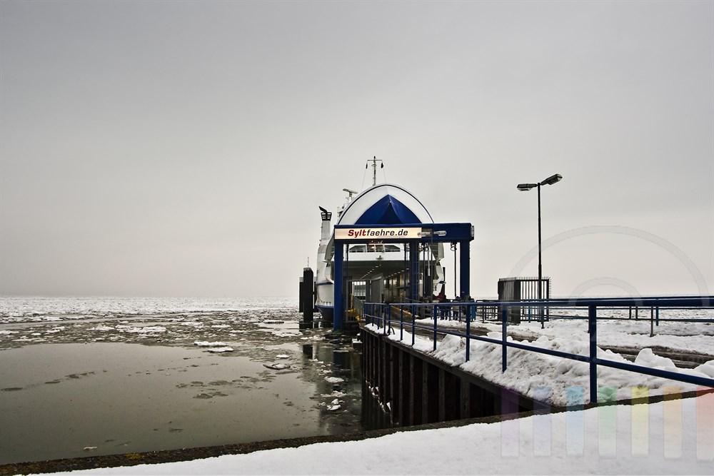 Sylt-Fähre mit geöffnetem Bugtor im Hafen von List/Sylt. Der Himmel ist bedeckt, auf der Nordsee treiben Eisschollen