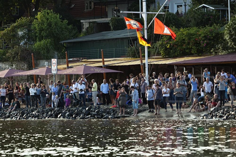 """zahlreiche Menschen stehen am Elbstrand vor der Kultkneipe """"Strandperle"""" in Hamburg-Oevelgoenne und Beobachten das Auslaufen des Kreuzfahrtschiffes """"Queen Mary 2"""". Viele fotografieren dabei, sommerlich"""