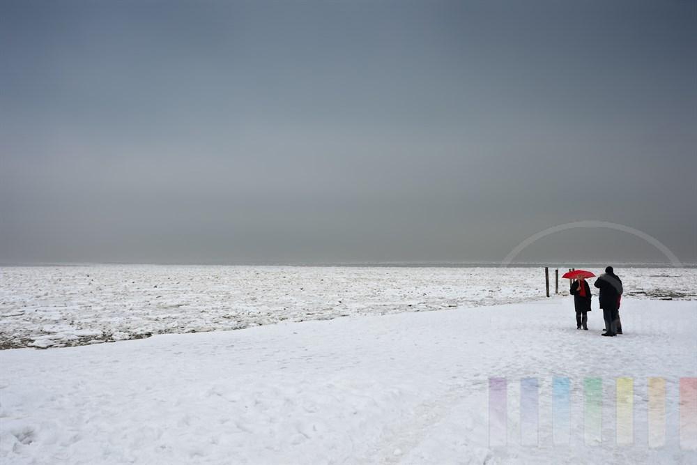 Menschengruppe mit knallrotem Regenschirm steht bei schlechtem Wetter an der vereisten Nordsee vor List/Sylt und unterhält sich - der Himmel ist bedeckt. Die Szene mutet ein wenig skurril an...