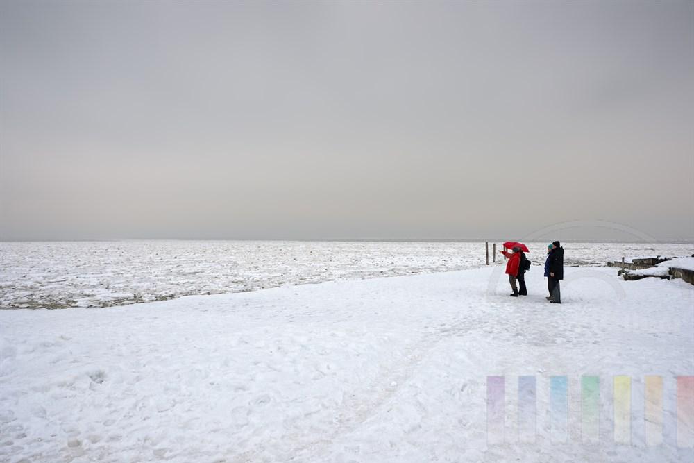 zwei ältere Urlauber-Paare stehen mit leuchtend rotem Regenschirm staunend an der mit Eisschollen bedeckten Nordsee vor List/Sylt