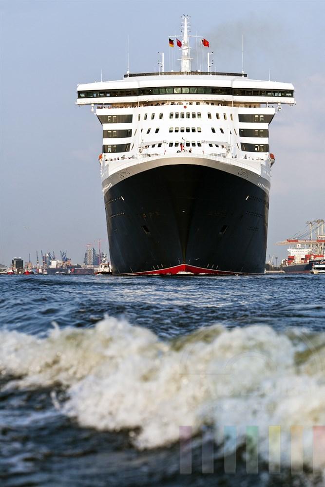 """Das Kreuzfahrtschiff """"Queen Mary 2"""" laeuft aus dem Hamburger Hafen aus, sonnig, Frontalansicht vom Wasser, Hochformat"""