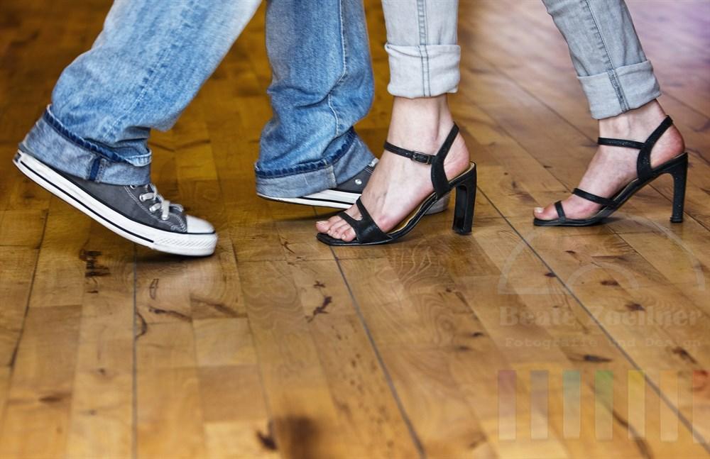 Fuesse von jungem Mann und junger Frau bewegen sich auf dem Parkett einer Tanzschule