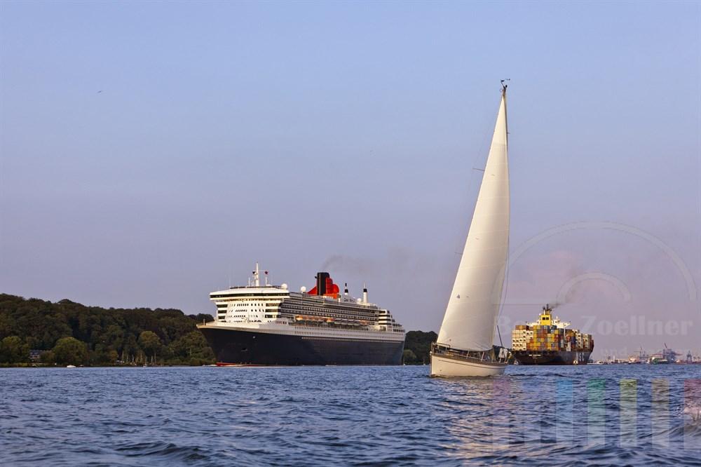 """Das Kreuzfahrtschiff """"Queen Mary 2"""",  eine Segelyacht und ein voll beladener Containerfrachter im sommerlichen Abendlicht auf der Elbe vor Hamburg-Blankenese"""