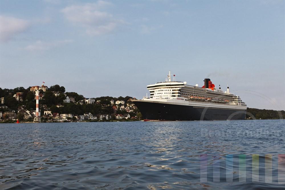 """Das Kreuzfahrtschiff  """"Queen Mary 2""""  laeuft aus dem Hamburger Hafen aus und faehrt elbabwaerts, Hoehe Blankenese, Abendstimmung. Fotografiert vom Wasser"""