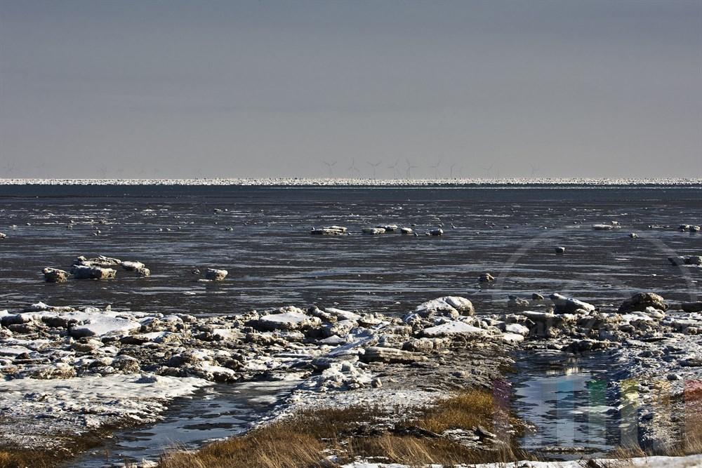 Blick vom Deich über das vereiste Wattenmeer vor Rantum auf der Insel Sylt - am Horizont sind zahlreiche Windkraftanlagen auf dem dänischen Festland zu erkennen