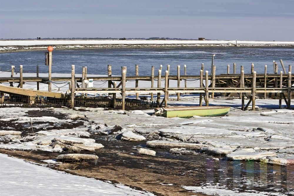 verlassener Bootshafen von Rantum/Sylt am vereisten Wattenmeer. Im Hintergrund gehen Spaziergänger auf dem Deich des Rantumbeckens entlang, sonnig