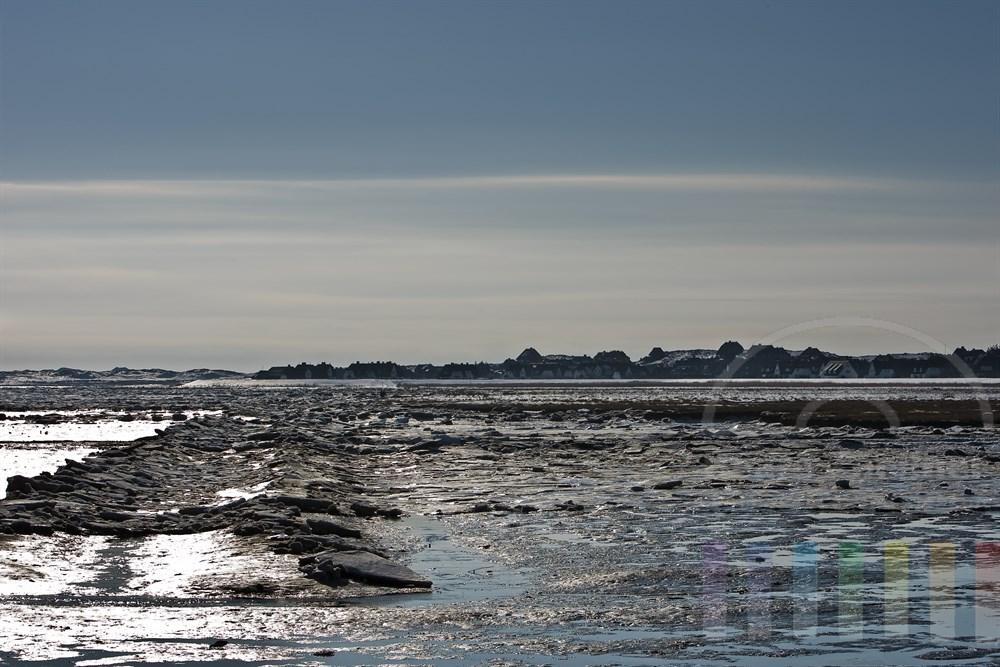 Blick über das vereiste Wattenmeer auf die am Rande der Dünen liegende Ortschaft Rantum/Sylt, sonnig, Gegenlicht