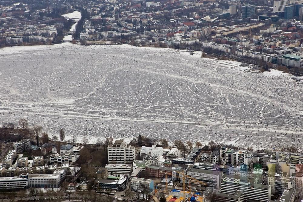 Blick ueber die zugefrorene Aussenalster mit zig tausenden Besuchern auf Binnenalster und Elbe