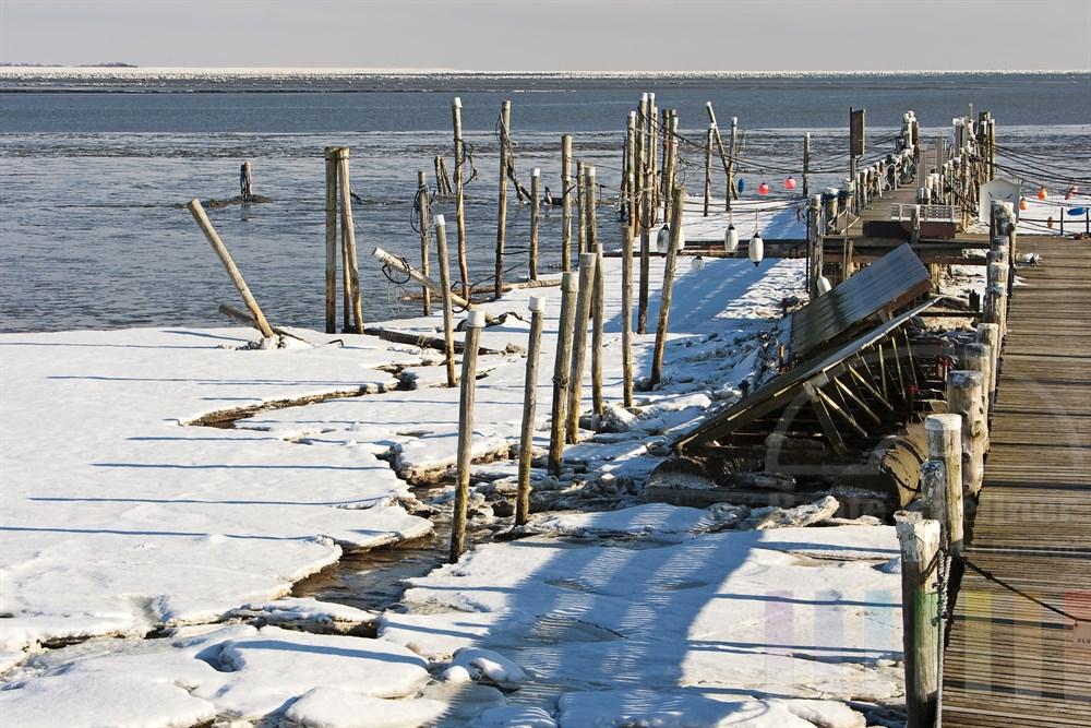 Der Bootshafen in Rantum am Sylter Wattenmeer ist vereist, sonnig. Der starke Eisgang hat einige Holzpfähle gekippt.