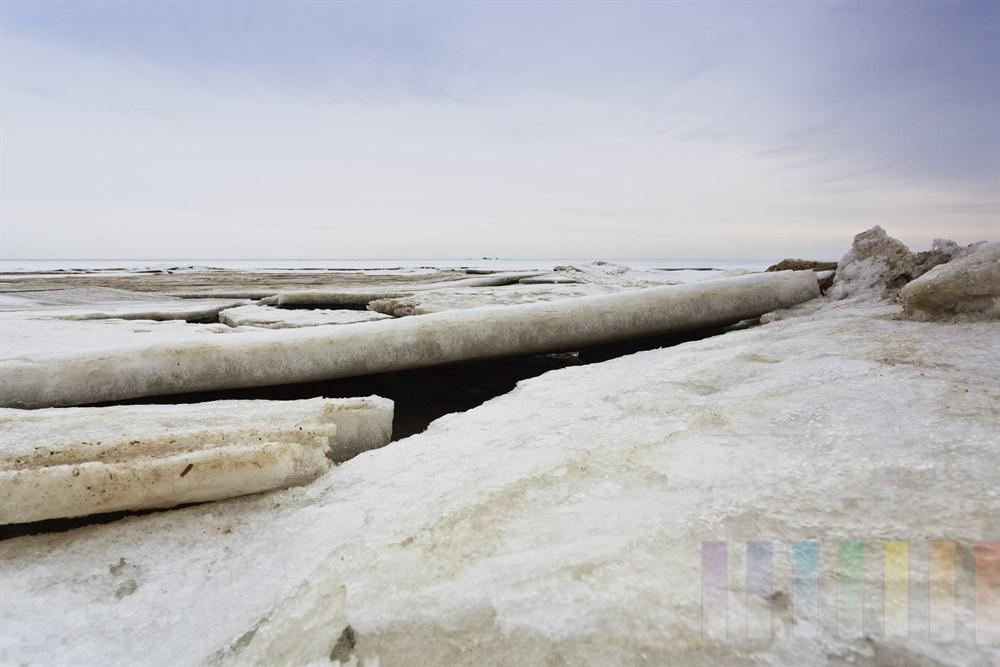Grosse Eisschollen haben sich am Strand durch die Gezeiten des Sylter Wattenmeeres uebereinander geschoben, Himmel bewoelkt