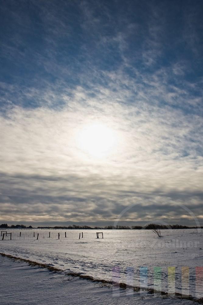 Winter-Landschaft in der Braderuper Heide/Sylt mit verharschter Schneedecke auf der das letzte Sonnenlicht vor einem Wetterwechsel refelktiert