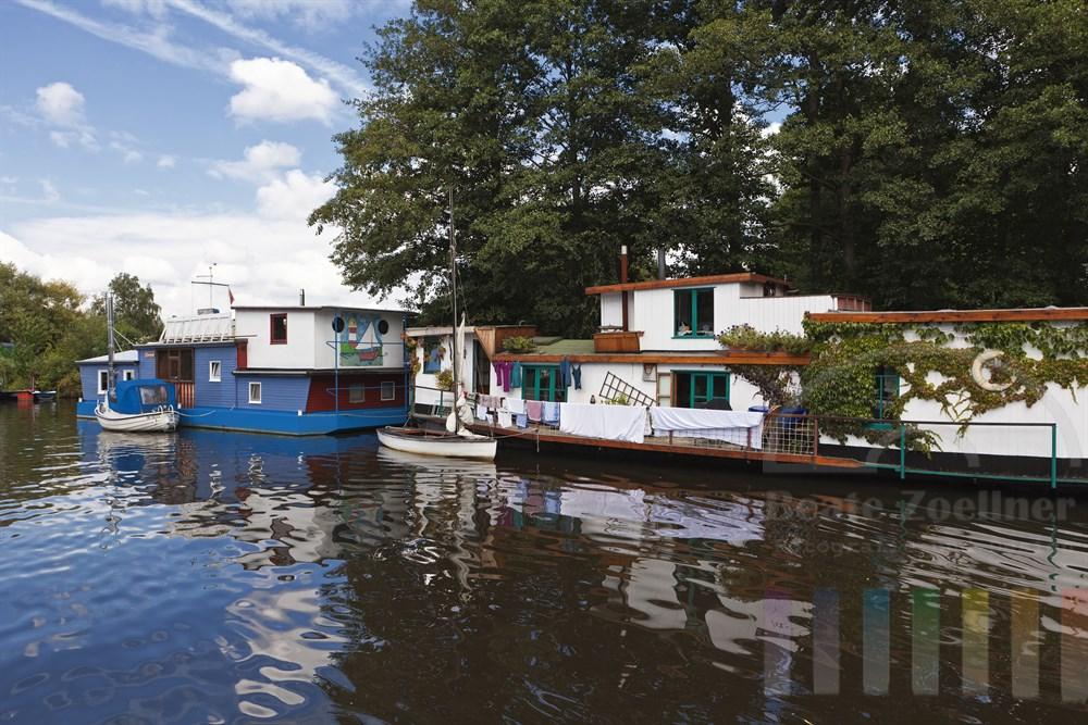 Bunte Hausboote liegen am Ufer der Dove-Elbe in Hamburg Reitbrook, Waesche haengt zum Trocknen ueber der Reling