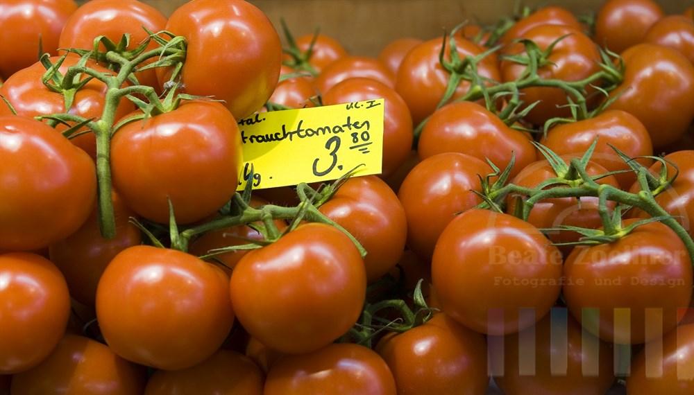 Reife italienische Strauchtomaten liegen appetitlich an einem Marktstand
