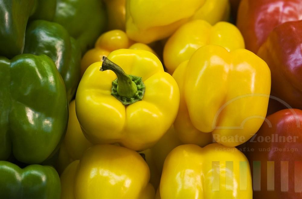 frische Paprika in den Farben grün, gelb und rot liegen nebeneinander zum Verkauf an einem Marktstand