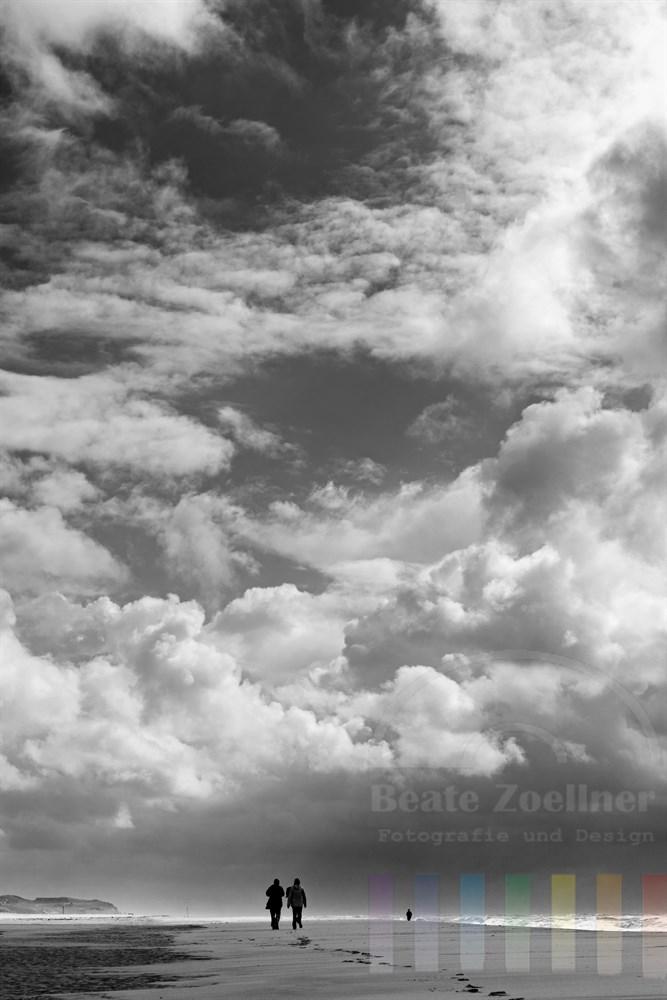 Ein Paar spaziert am einsamen Sylter Weststrand unter Wolkentürmen