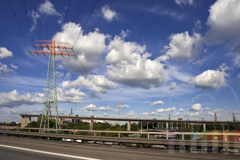 Blick von der Autobahn kurz vor dem Elbtunnel auf die Köhlbrandbrücke im Hamburger Hafen. Darüber wölbt sich blauer Himmel mit schönen Wolken