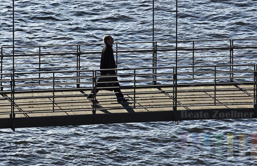 Mann geht über die moderne Kibbelstegbrücke in der historischen Hamburger Speicherstadt, die über das Wasser des Zollkanals führt. Gegenlicht