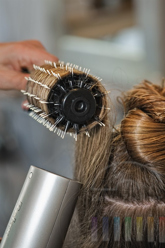 Hand einer Friseurin foent die langen, nassen Haare einer Kundin über eine Rundbürste in Form
