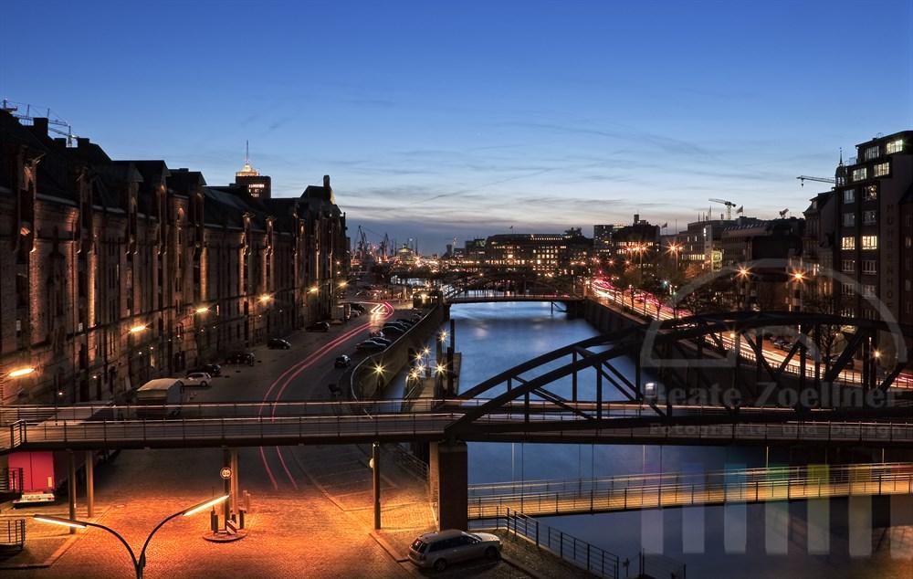 Blick auf die Hamburger Speicherstadt, den Hafen und die Brücken über den Zollkanal zur Blauen Stunde
