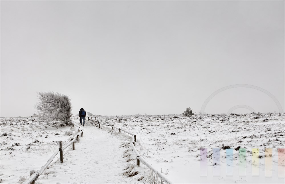 zwei Spaziergänger in Winterlandschaft, Himmel bedeckt