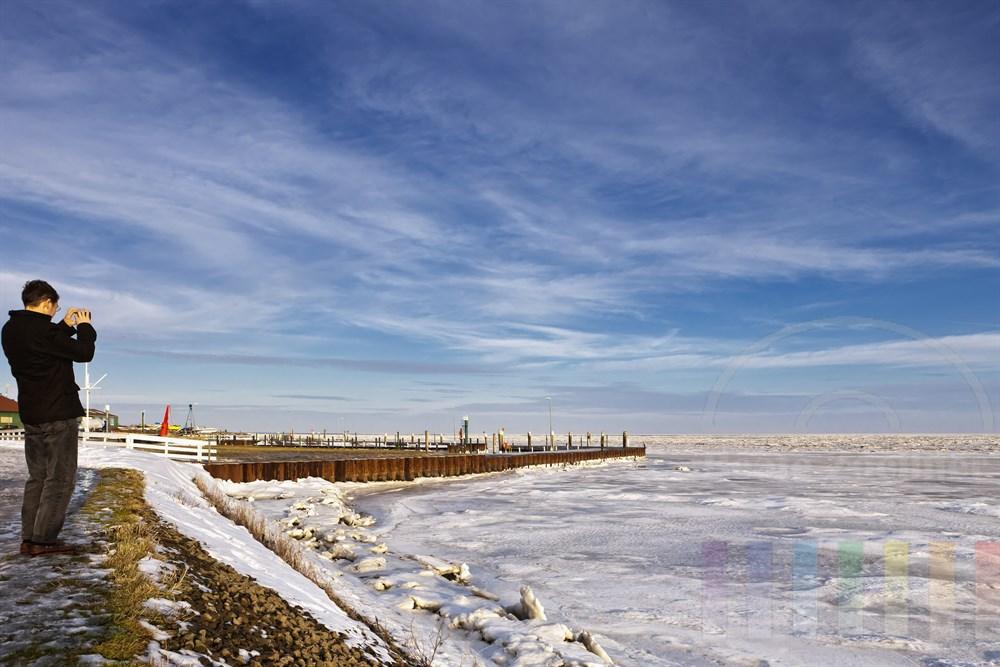 Urlauber fotografiert das vereiste Wattenmeer am Munkmarscher Hafen, sonnig