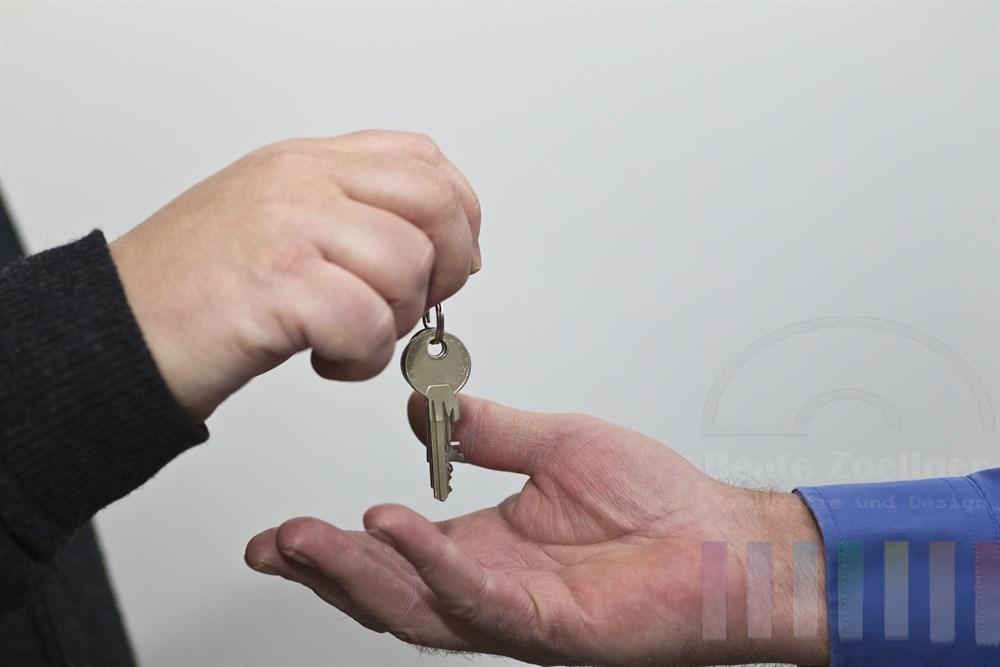 Wohnungsschluessel wird von einer Maennerhand in eine andere gegeben
