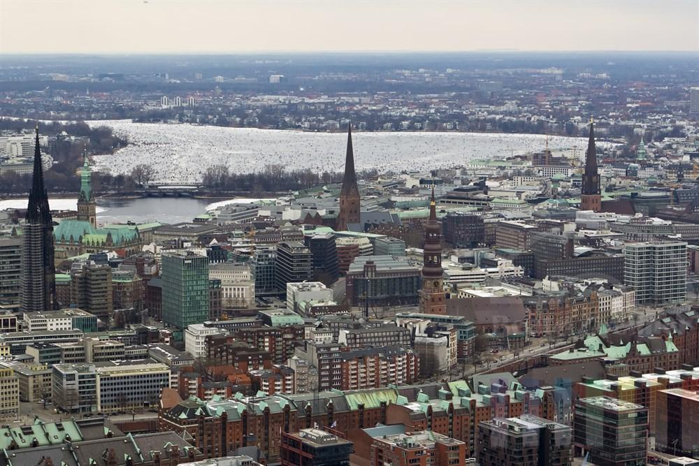 Blick über die Hamburger Innenstadt mit Hauptkirchen und Rathaus auf die zugefrorene Aussenalster auf der sich tausende Menschen tummeln.