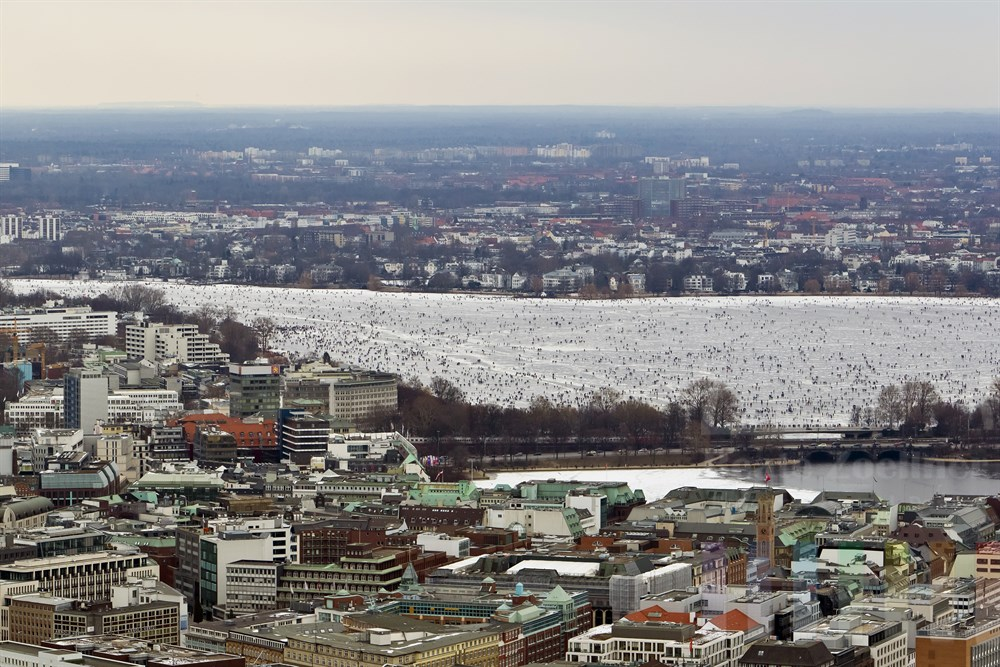 Blick über die Hamburger Innenstadt  auf die zugefrorene Aussenalster auf der sich tausende Menschen tummeln.