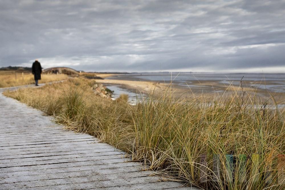 Mann im Mantel geht auf reifbedecktem Holzbohlenweg am Sylter Wattenmeer entlang