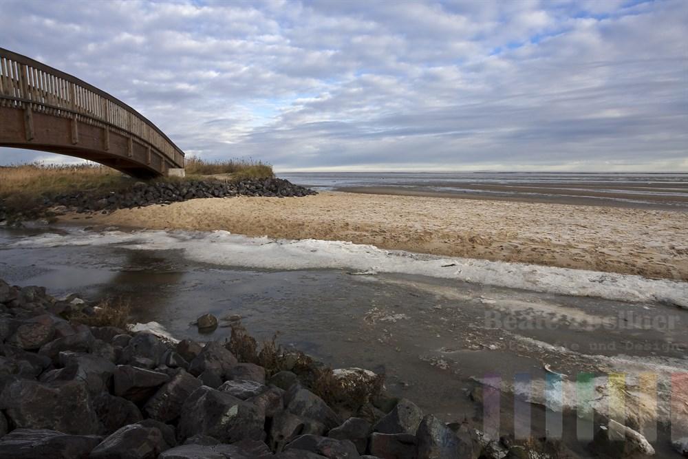 Winterlich: Die Holzbrücke in Munkmarsch/Sylt führt über einen Priel und Marschwiesen direkt am Strand des Wattenmeeres