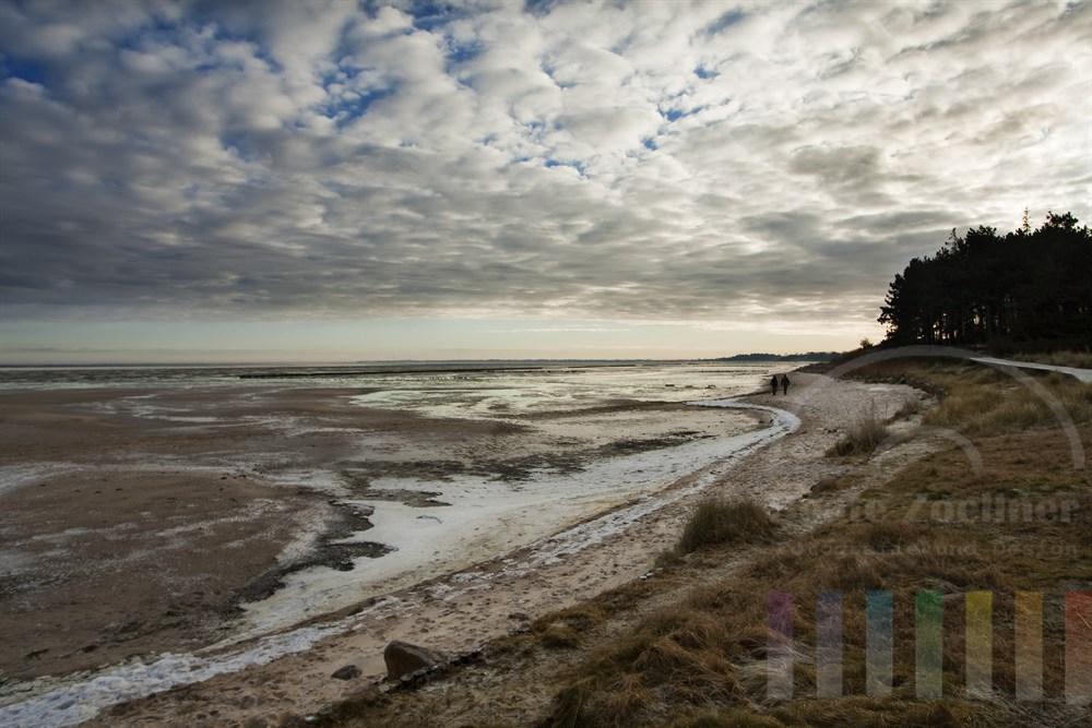 Winterlich einsame Landschaft am Sylter Wattenmeer. Nur zwei Menschen spazieren am Strand entlang