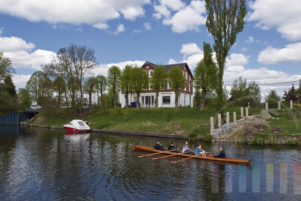 Blick von der Dove-Elbe ueber ein Ruderboot mit freundlich winkenden Sportlern auf das Ortsamt der Vier- und Marschlande an der Strasse Kurfürstendeich 41