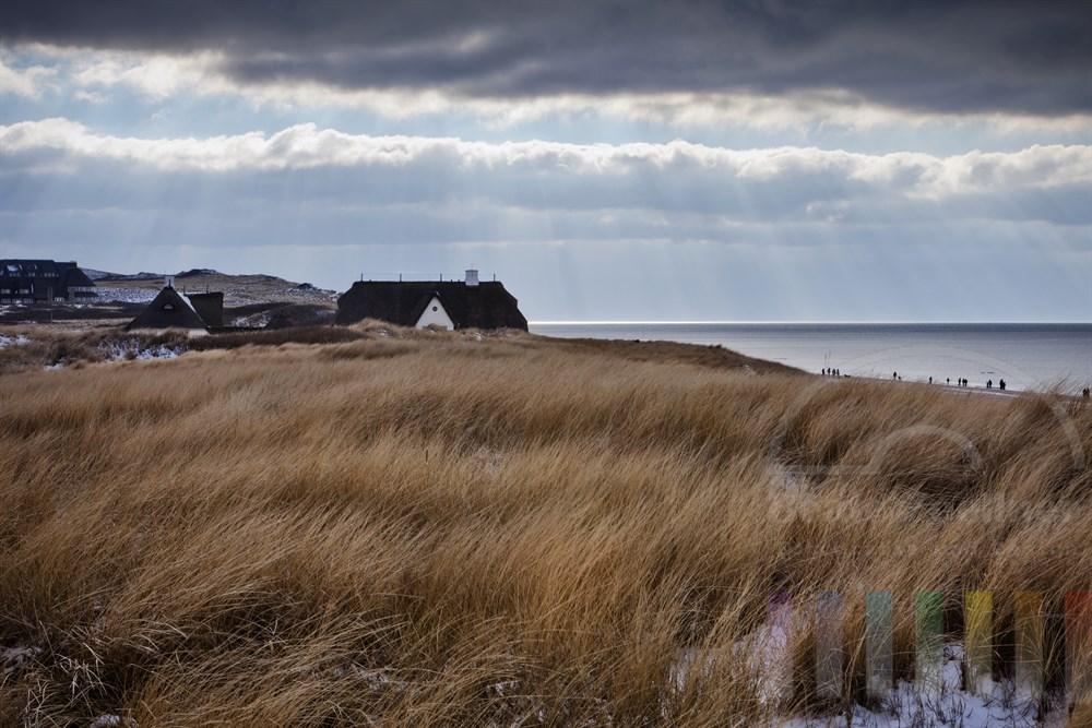 """Blick auf Haus Kliffende am Roten Kliff in Kampen/Sylt, winterlich. Einige Urlauber spazieren am Nordseestrand entlang. Am linken Bildrand die """"Sturmhaube"""" und dahinter das Hotel """"Rungholt"""""""