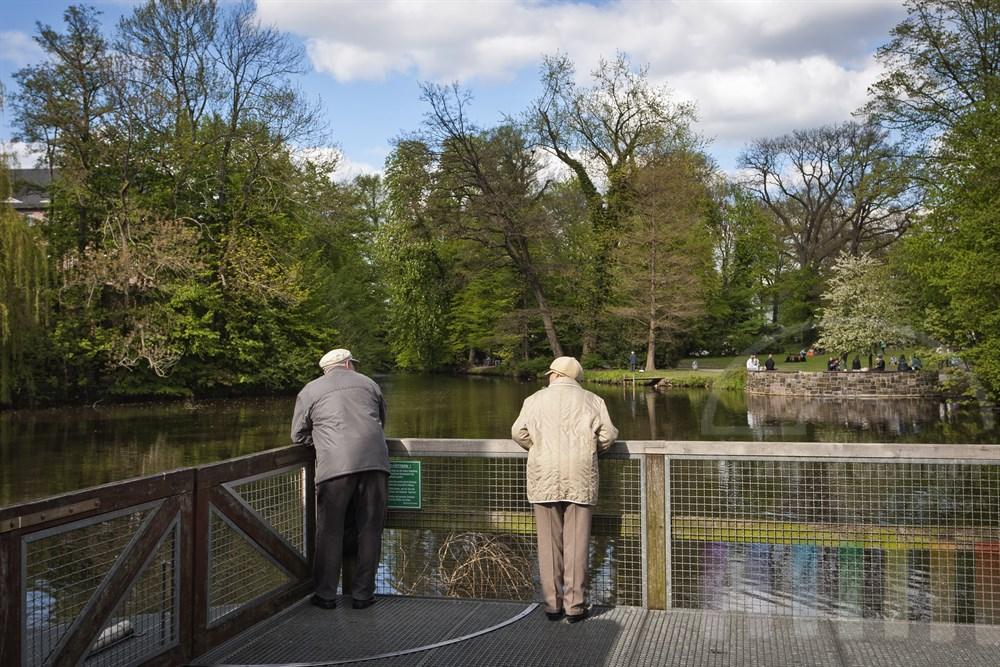 Rentner-Paar steht auf einem Podest, beide schauen sich an, im Hintergrund der frühlingshafte Bergedorfer Schlosspark