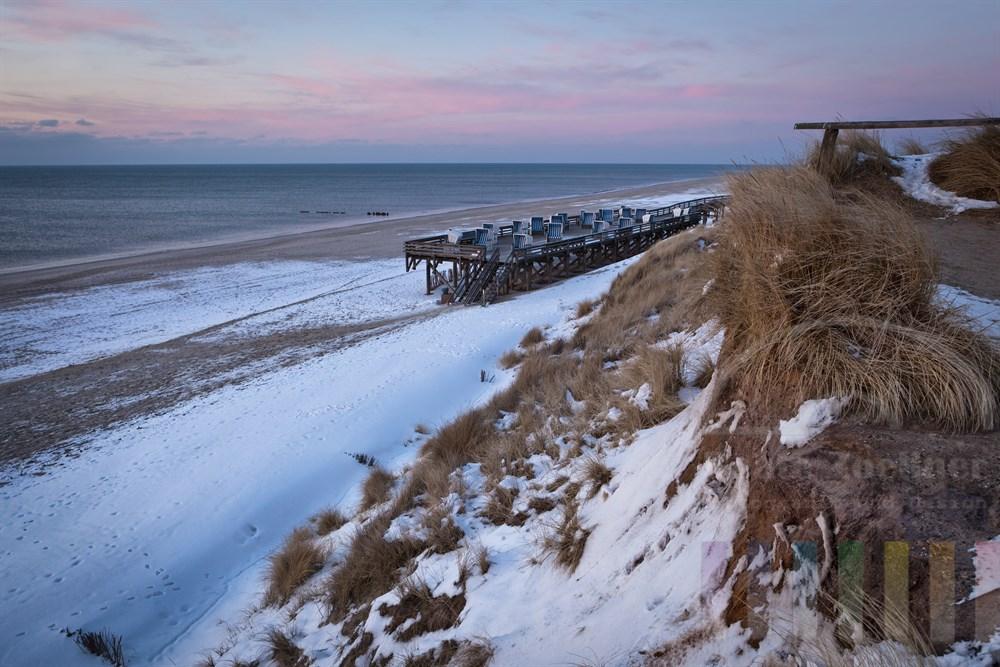 Letztes Tageslicht scheint auf das verschneite Rote Kliff und den Strand in Kampen/Sylt