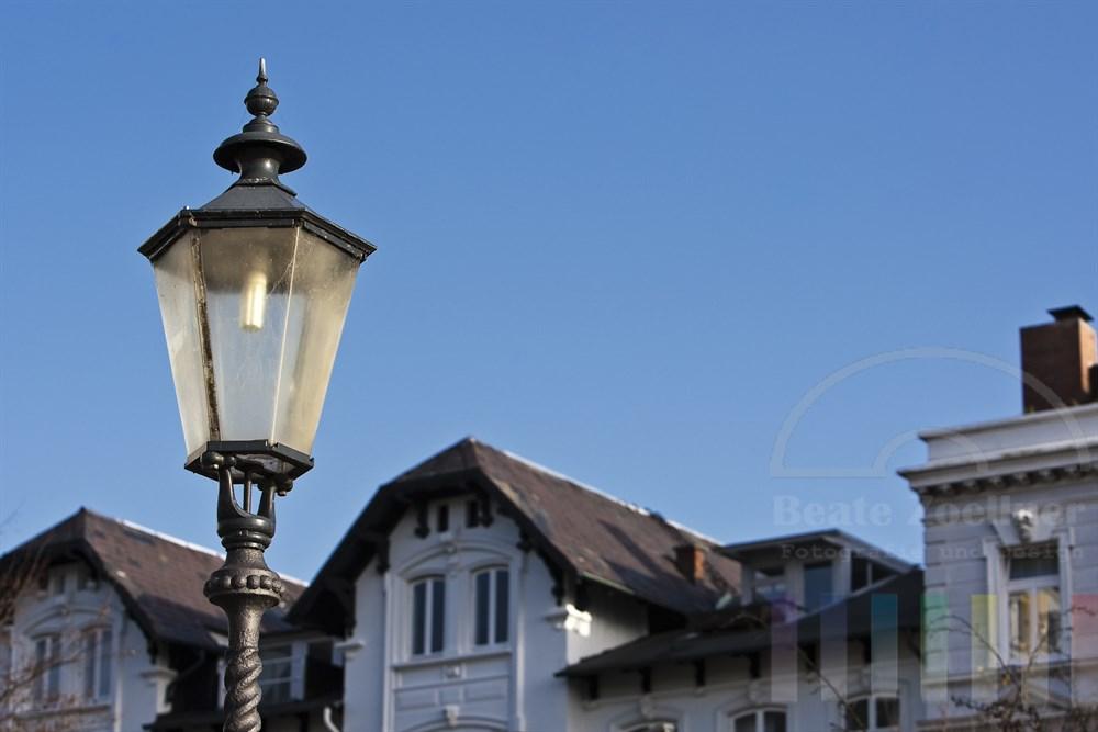 historische Strassenlaterne mit Energiesparlampe vor Wohnhäusern in der Strasse Rainvilleterrasse in Hamburg-Ottensen, Sonnenschein