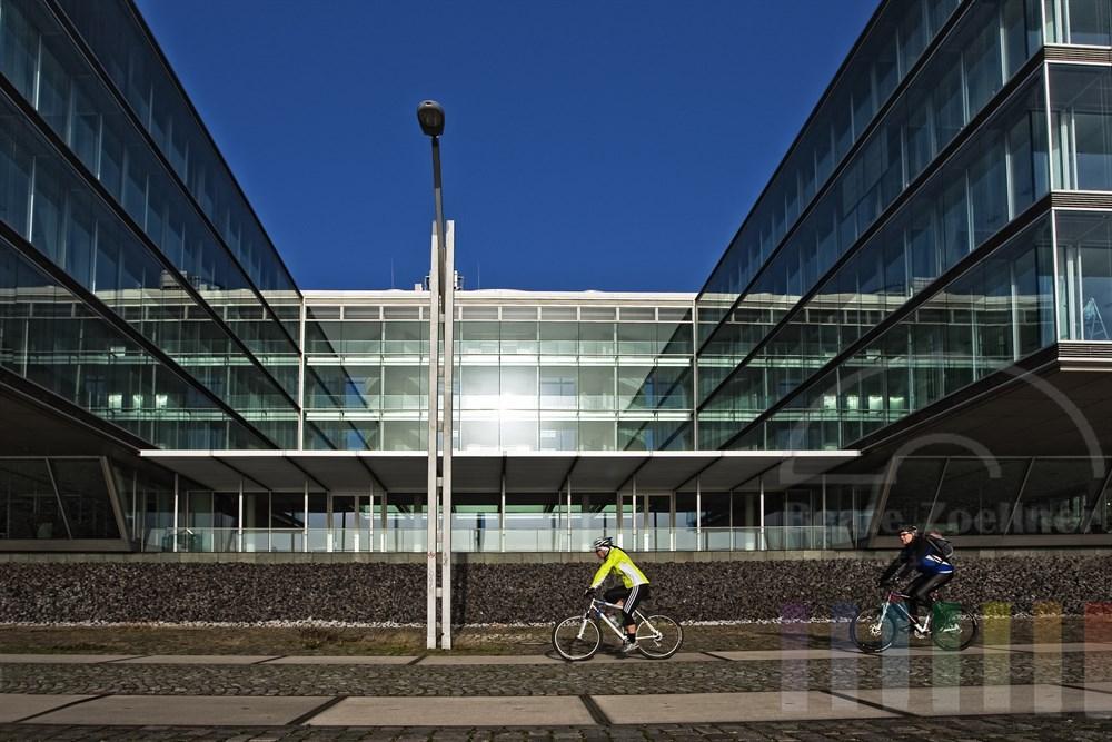 Radfahrer auf der Elbpromenade in Hamburg-Neumühlen vor modernen Bürogebäuden, sonnig