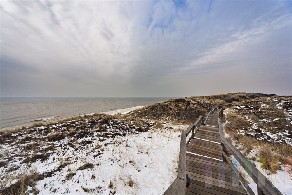 Holzsteg fuehrt durch die verschneiten Duenenlandschaft in Wenningstedt an der Sylter Westkueste