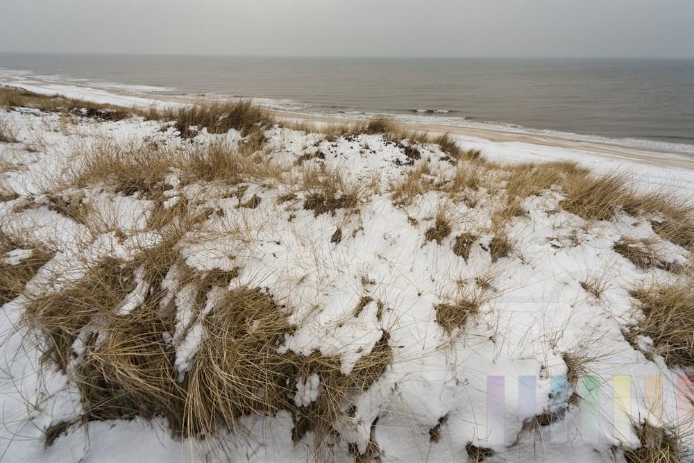 Blick über verschneite Dünen auf den menschenleeren Strand von Wenningstedt auf der Insel Sylt