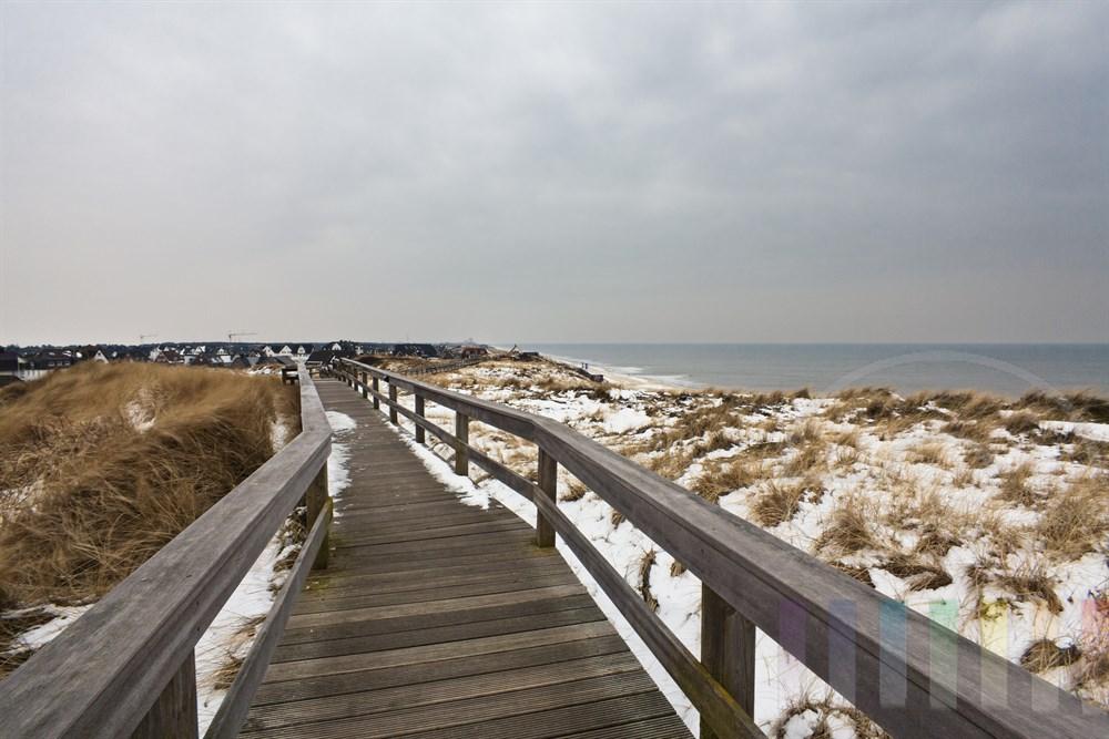 Holzsteg fuehrt durch die verschneiten Duenenlandschaft nach Wenningstedt an der Sylter Westkueste