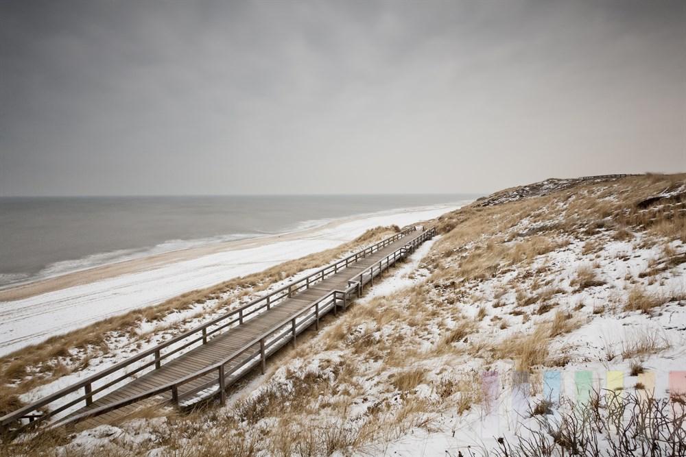 Blick über den verschneiten und menschenleeren Strand in Wenningstedt/Sylt, bewölkt