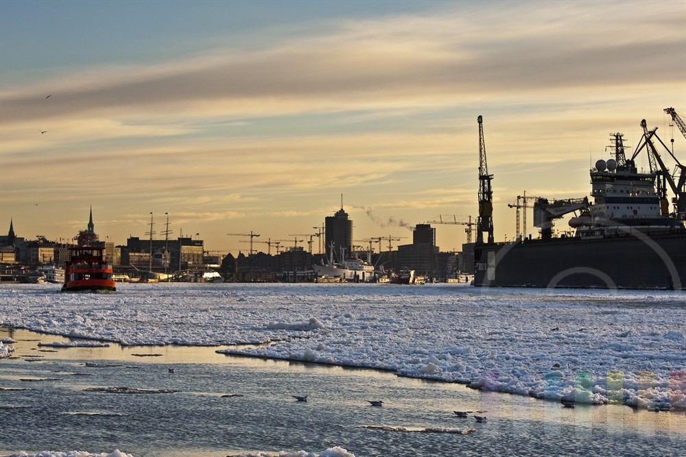 Wintermorgen im Hamburger Hafen: Blick über das Treibeis auf der Elbe zu den Landungsbrücken