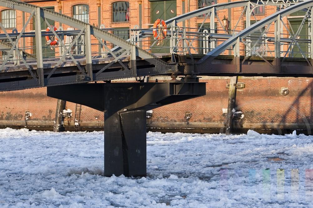 Stahlbruecke zum Schiffsanleger am Hamburger Fischmarkt im Winter bei Eisgang auf der Elbe - im Hintergrund die Fassade der Fischauktionshalle die von der Wintersonne angestrahlt wird