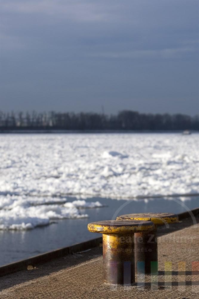 Poller am Schiffsanleger Hamburg-Oevelgönne glänzen im Sonnenlicht während auf der Elbe dicke Eisschollen treiben